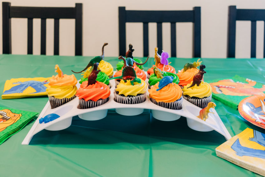 Cupcakes with dinosaur decorations and a 2 candle
