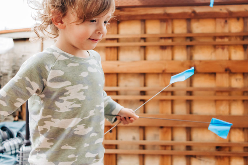 Toddler with a camouflage raglan sweater and little blue flags