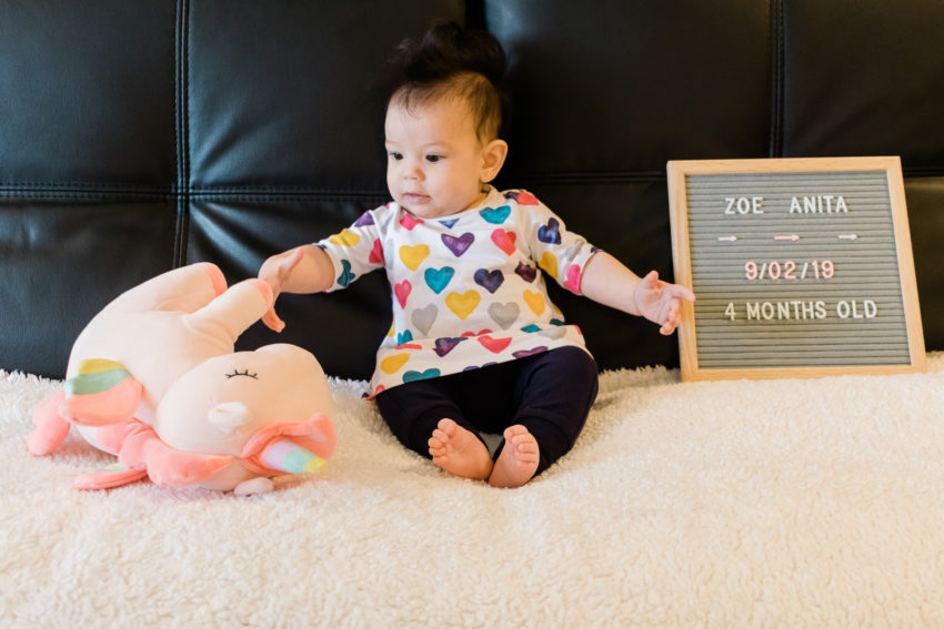 A baby knocking over a stuffed unicorn