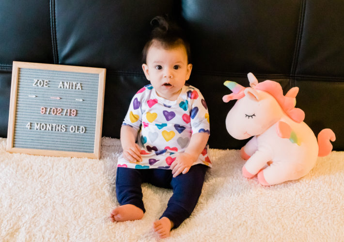 4 month old in colorful heart dress and blue pants